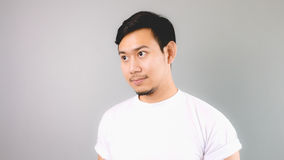A man looking out. An asian man with white t-shirt and grey background royalty free stock image