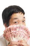 Man Looking Out From Behind A Fan Of Fifties. Man looking out from behind a fan of fifty dollar bills he is holding Royalty Free Stock Image