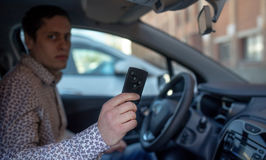 Man looking out from car window and holding a car alarm key Stock Photography