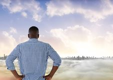 Man looking out at colourful city skyline with smoke in front of him. Digital composite of Man looking out at colourful city skyline with smoke in front of him stock photography