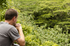 Man looking out. Man looking out and gazing at the open vegetation and leaning on a fence Stock Image