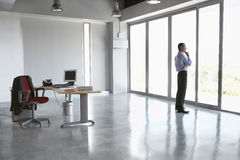 Man Looking Out Of Glass Door In Empty Office Stock Images
