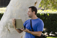 Man looking out while holding a lap top outside. stock photo