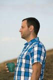 Man looking out holding a teal cup. Man standing and looking out onto a hillside holding a cup in his hand wearing a plaid shirt Royalty Free Stock Photo