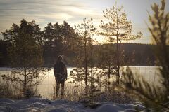 Man looking out over frozen lake at sunset, enjoying the beauty of nature.