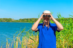 Man is looking out for prey with binoculars Royalty Free Stock Photo