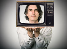 Man looking out of a retro television. Happy man looking out of a retro television, holding it in his hands Stock Photo