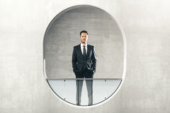 Man looking out of round window Stock Photos