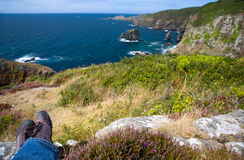 Man looking out on rugged coast after hike on Sark, UK Stock Image