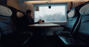 Stocker enjoying train ride after doing the job. Man looking out the train window after finishing shooting video of outside scenes stock footage