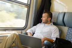 Man looking out the train window laptop Stock Images