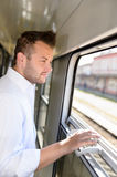 Man looking out the train window smiling Royalty Free Stock Photos