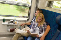 Man looking out train window woman reading Royalty Free Stock Images