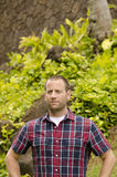 Man looking out. Man looking out wearing a plaid shirt in a tropical environment Stock Image