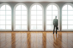 Man looking out of window. Back view of young businessman in suit looking out of window in modern interior with clean shiny wooden floor. 3D Rendering Royalty Free Stock Photo