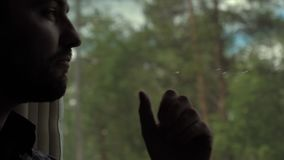 Man looking out window with chin on hand in a train, serious expression. Close up.Man looking out window with chin on hand in a train, serious expression stock video footage