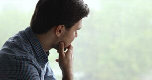 Man looking out the window feels unhappy goes through divorce