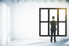 Man looking out the window in light empty room Stock Images