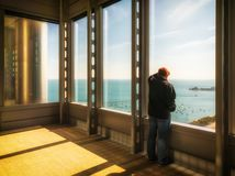 A man looking out of the window of a skyscraper. Lake Michigan, royalty free stock image