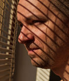 Man looking out a window though blinds Stock Photography