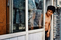 Man looking outside of his home to the street in a typical city hutong stock images