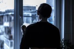 Man Looking Outside Near Clear Glass Window Stock Photography