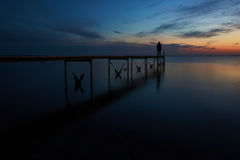 Man looking over the fjord after sunset. At Vadum beach in Denmark Stock Photo