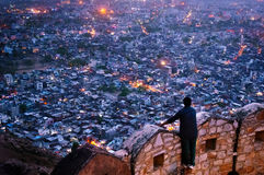 Man looking over the fort walls of Nahargarh at Jaipur city. Man looking over the fort walls of Nahargarh to see the lights of Jaipur city at night. This is a Stock Photos