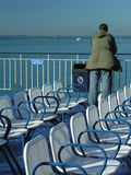 Man looking over railing. A man stood on upper deck of a ferry looking out to sea, with two rows of empty passenger seats in the foreground Royalty Free Stock Photo
