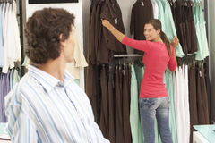 Man looking over shoulder at girlfriend choosing tops from rail in clothes shop, smiling, focus on background Stock Photo