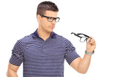 Man looking at a pair of glasses Stock Photo