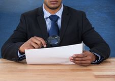 Man looking at paper with magnifying glass at desk Stock Images