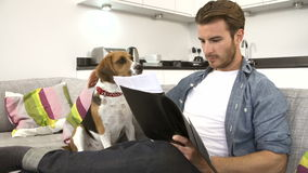 Man Looking At Paperwork And Playing With Pet Dog At Home stock footage