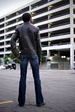 Man looking at parking garage. A view of the back of a young 22-year old man as he looks across the street at a large, multi-level city parking garage royalty free stock photo