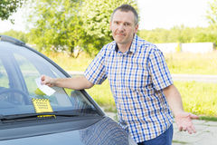 Man looking on parking ticket. Unhappy man looking on parking ticket placed under windshield wiper Stock Images