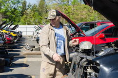 Man is looking for parts on a junk yard Royalty Free Stock Photos