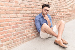 Man looking pensive while sitting on the sidewalk Royalty Free Stock Image
