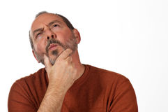 Man looking perplexed. Middle aged man with hand on beard looking up thinking Royalty Free Stock Image
