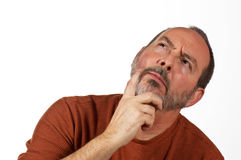 Man looking perplexed. Middle aged man with hand on beard looking up thinking Stock Photos