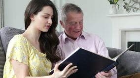 Man Looking At Photo Album With Adult Granddaughter