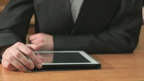 Man looking at photos using computer tablet. Close-up of hand of man dressed in black suit sits at desk at office the resting and looking at favorite photos stock video