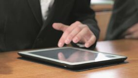 Man looking at photos using computer tablet. Close-up of hand of man dressed in black suit sits at desk at office the resting and looking at favorite photos stock footage