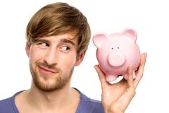 Man looking at piggy bank suspiciously Stock Photo