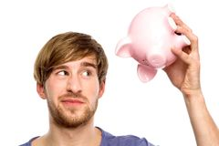Man looking at piggy bank suspiciously Stock Photography