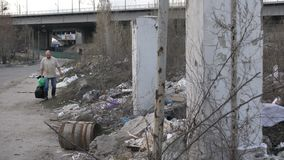 Man looking for plastic at garbage dump in city