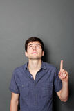 Man looking and pointing up to copy space Stock Images