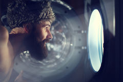 Man looking through  porthole of a ship Royalty Free Stock Images