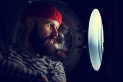 Man looking through  porthole of a ship Stock Photo