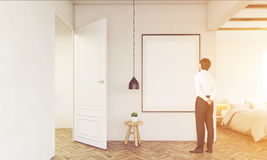 Man looking at a poster in his bedroom, toned. Rear view of businessman standing in his bedroom and looking at blank framed poster on the wall. Concept of home Stock Photos