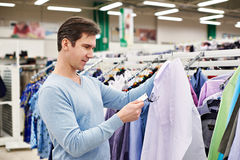 Man looking at price tag of goods. Man looking at a price tag of goods Royalty Free Stock Photos